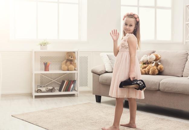 Menina bonita com os sapatos da mãe. pequena fashionista vai experimentar salto alto, se divertir em casa, copia espaço