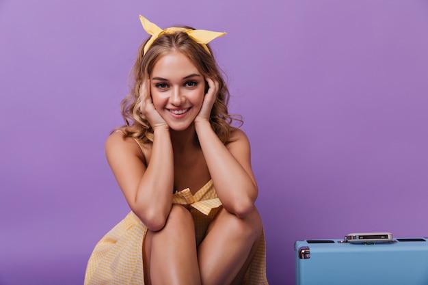 Menina bonita com pele bronzeada arrepiante. alegre mulher turística sentada no pastel com bagagem.