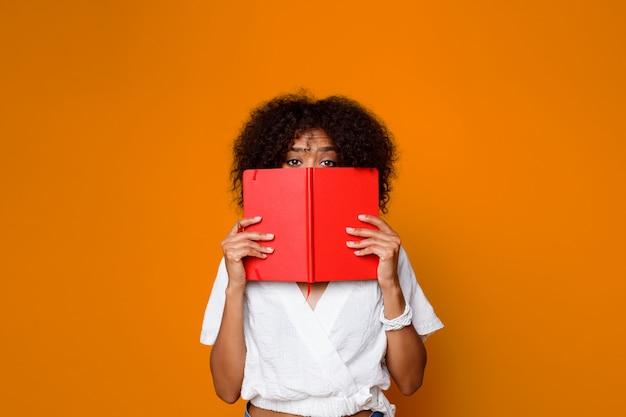 Menina bonita com pele escura, escondendo o rosto por trás do livro, olhando para a câmera. fundo laranja.