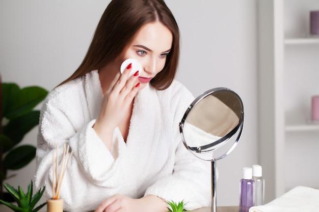 Menina bonita com pele saudável faz maquiagem