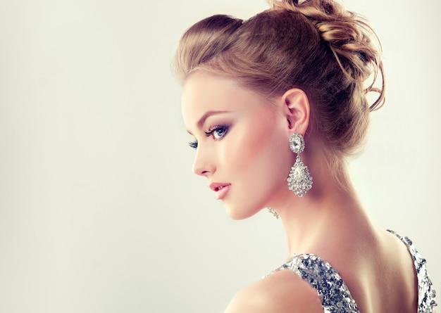 Menina bonita com penteado elegante e grandes brincos de jóias