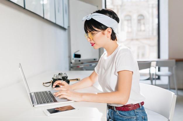 Menina bonita com penteado vintage usando laptop para trabalhar, sentada em casa em uma grande sala de luz