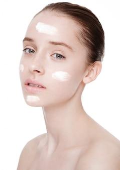 Menina bonita com retrato de maquiagem natural creme para o rosto em fundo branco