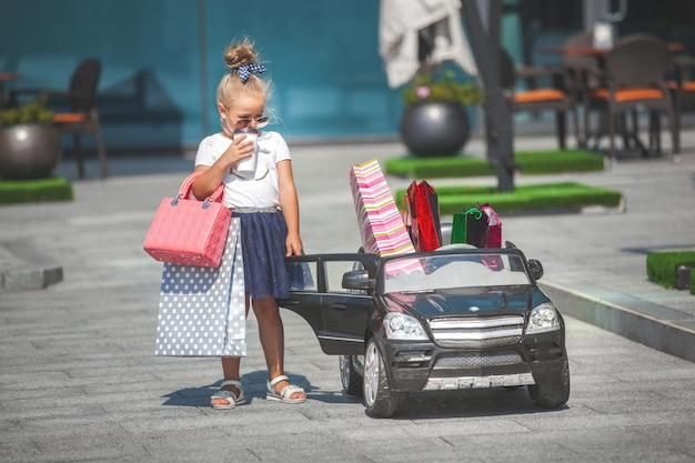 Menina bonita com sacos de compras em um minicar