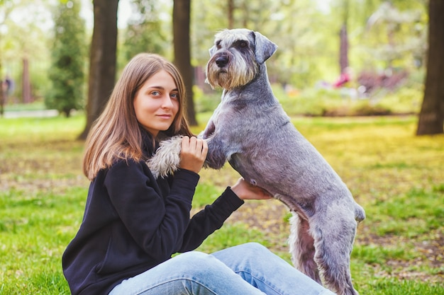Menina bonita com seu cachorro schnauzer no parque natural ao ar livre