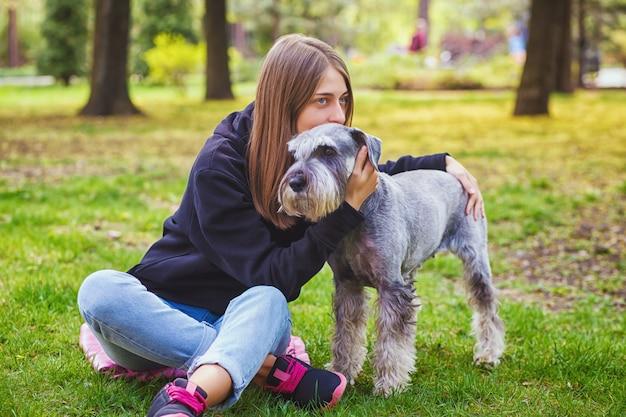 Menina bonita com seu cachorro schnauzer no parque natural