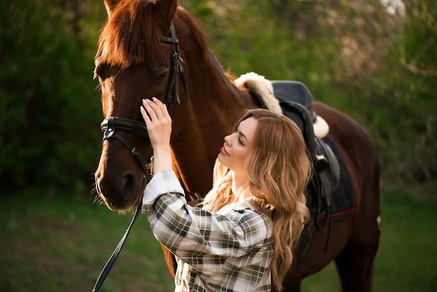 Menina bonita com seu cavalo e belo pôr do sol quente na primavera floresta.