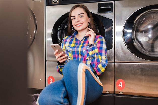 Menina bonita com smartphone na mão ouve música, apoiando-se em uma máquina de lavar roupa em público