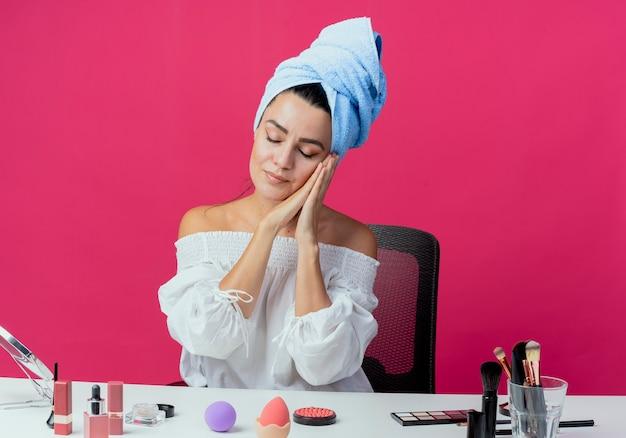 Menina bonita com sono embrulhada em toalha de cabelo, senta-se à mesa com ferramentas de maquiagem de mãos dadas perto do rosto isolado na parede rosa