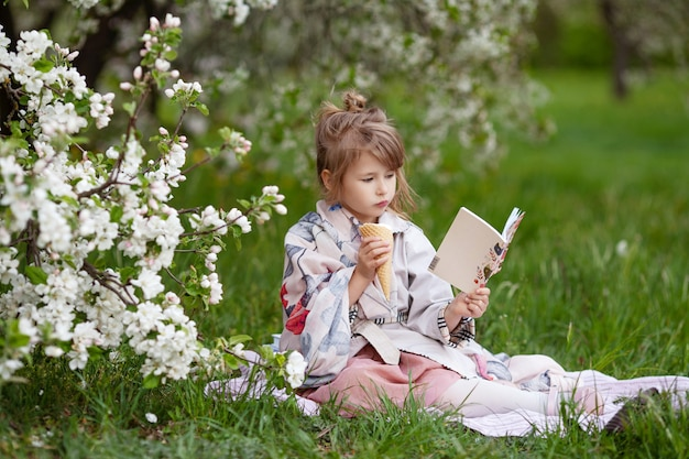 Menina bonita com sorvete, lendo um livro no parque. criança ao ar livre em um jardim florido de primavera