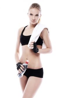 Menina bonita com toalha e garrafa de água