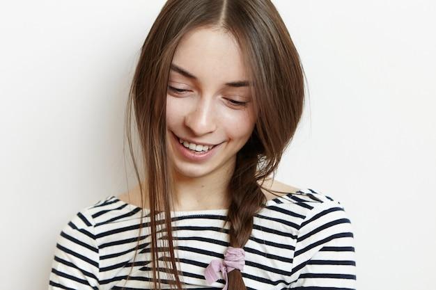 Menina bonita com trança de cabelo bagunçado olhando para baixo com sorriso tímido fofo