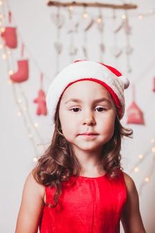 Menina bonita com um boné de papai noel decorando a árvore de natal