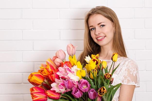 Menina bonita com um buquê de tulipas
