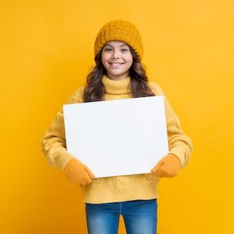 Menina bonita com um cartaz nas mãos dela