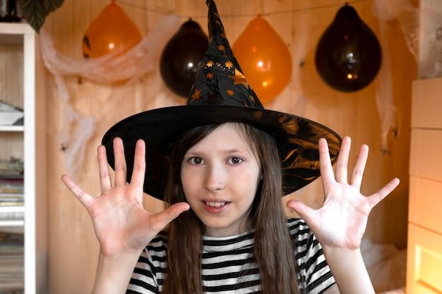 Menina bonita com um chapéu de mago dizendo boo com um gesto assustador crianças de halloween retrato