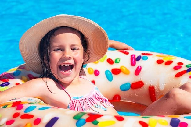 Menina bonita com um chapéu está tomando banho em um anel inflável na piscina