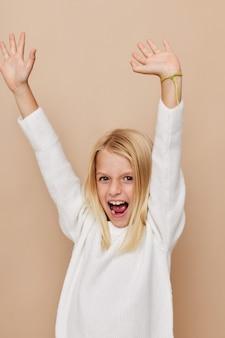 Menina bonita com um suéter fazendo caretas conceito de estilo de vida para crianças