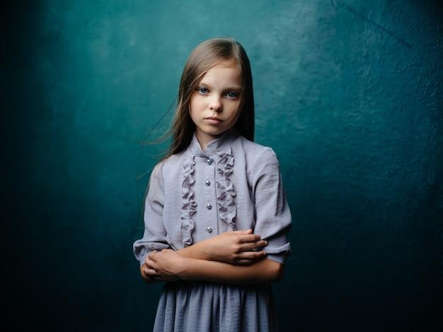 Menina bonita com um vestido de verão cinza sobre fundo turquesa