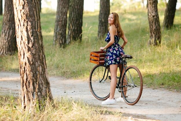Menina bonita com uma bicicleta na floresta.