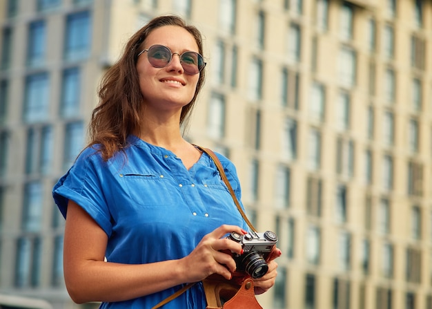 Menina bonita com uma câmera em um vestido azul no fundo do edifício