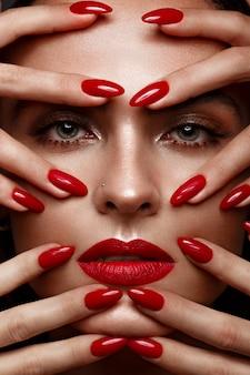 Menina bonita com uma maquiagem clássica e unhas vermelhas, design de manicure, rosto de beleza
