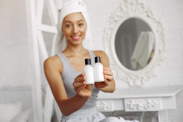 Menina bonita com uma toalha mostrando produtos de beleza
