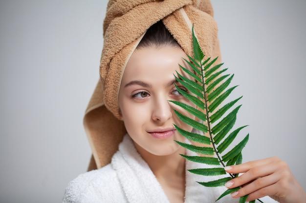 Menina bonita com uma toalha na cabeça depois de tomar banho