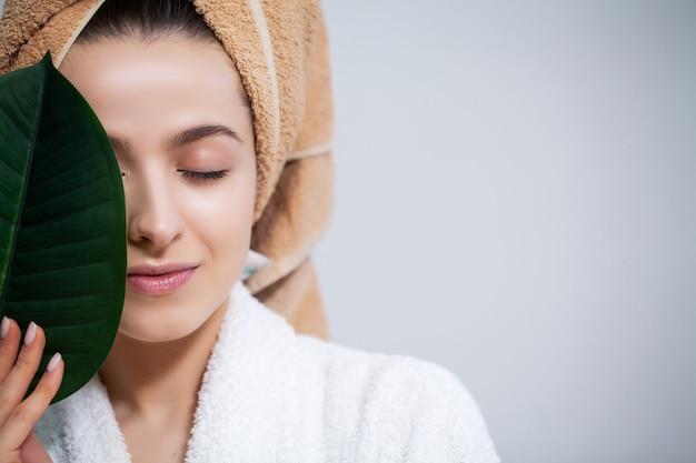 Menina bonita com uma toalha na cabeça e uma folha verde depois de tomar banho