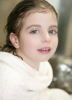 Menina bonita com uma toalha no banheiro