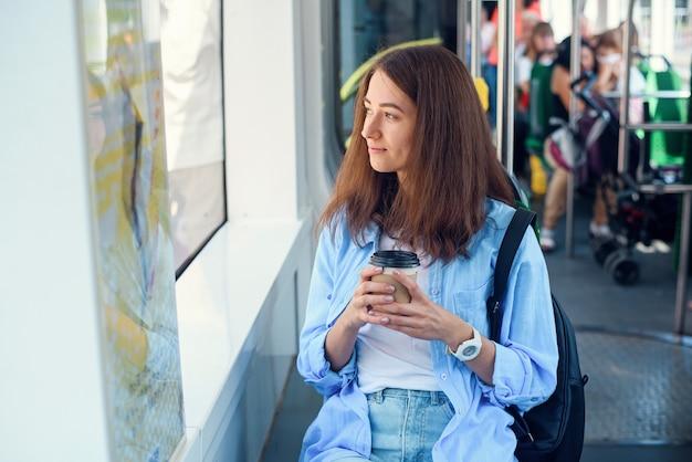 Menina bonita com uma xícara de café delicioso cavalga para a universidade em transporte público.