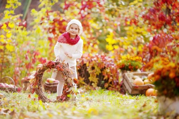 Menina bonita com uva vermelha deixa grinalda no parque outono.