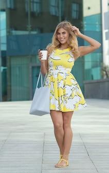 Menina bonita com vestido de verão na rua com café da manhã