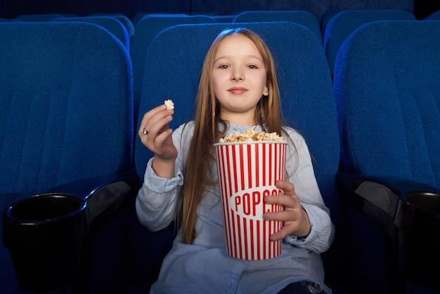 Menina bonita comendo pipoca, assistindo filme no cinema.