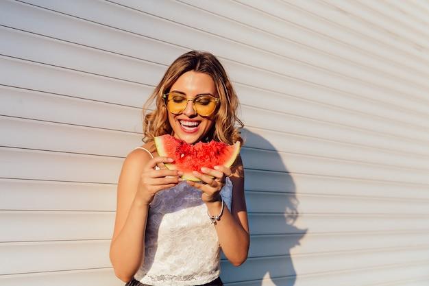 Menina bonita comendo uma melancia, usando óculos escuros amarelos, aproveitando os dias de verão