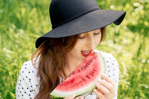 Menina bonita, comer pedaço de melancia