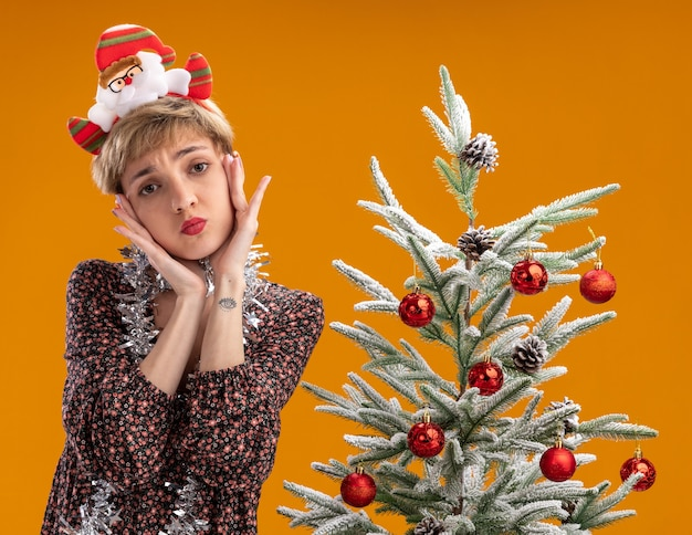 Menina bonita confusa com bandana de papai noel e guirlanda de ouropel no pescoço em pé perto da árvore de natal decorada, olhando para a câmera, mantendo as mãos no rosto isoladas em fundo laranja