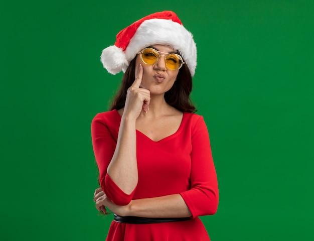Menina bonita confusa com chapéu de papai noel e óculos, olhando para o lado, mantendo a mão no queixo isolado na parede verde com espaço de cópia
