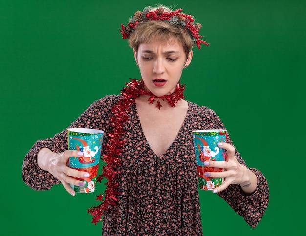 Menina bonita confusa usando coroa de flores de natal e guirlanda de ouropel em volta do pescoço segurando copos de plástico de natal, olhando para um deles isolado no fundo verde