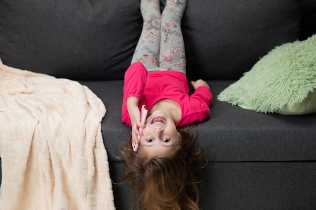 Menina bonita consideravelmente pequena que relaxa rindo no sofá ao falar ao telefone em casa.