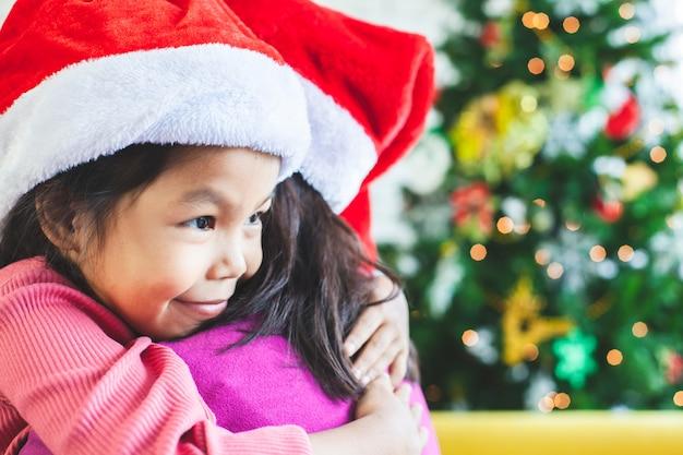 Menina bonita criança asiática, abraçando a mãe com amor na celebração de natal