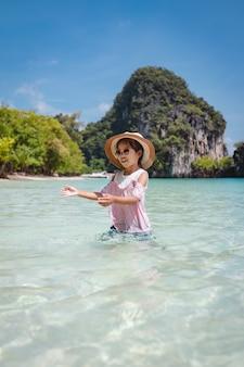 Menina bonita criança asiática com chapéu e óculos de sol, se divertindo para brincar no mar.