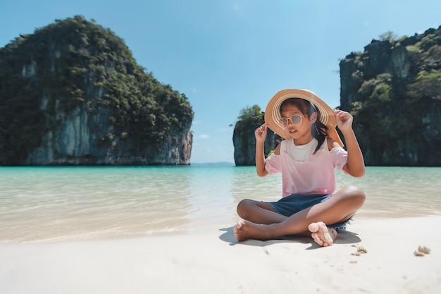 Menina bonita criança asiática com chapéu e óculos de sol, sentado na praia e brincando com areia.