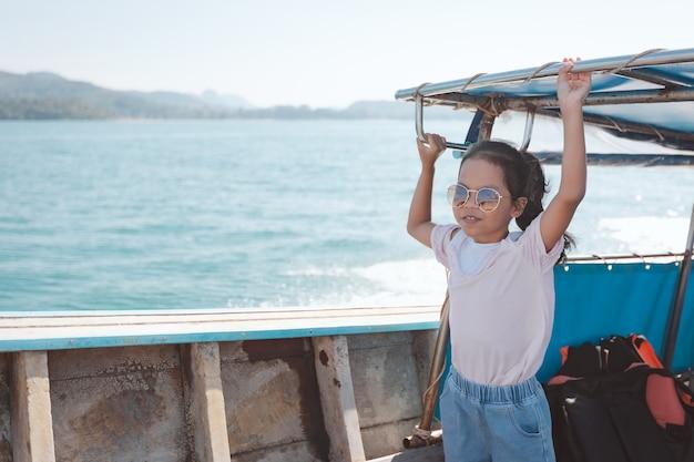 Menina bonita criança asiática em pé no barco longtail viajar no mar.