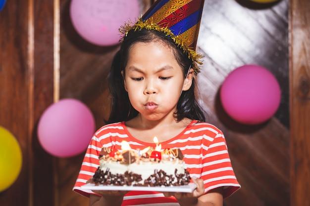 Menina bonita criança asiática está soprando velas no delicioso bolo de aniversário na festa com diversão e felicidade
