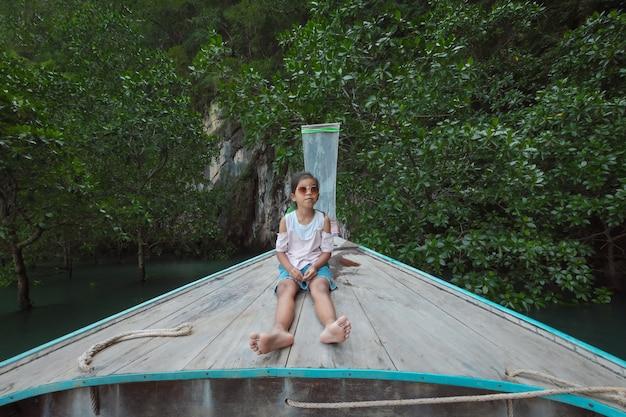 Menina bonita criança asiática sentada na cabeça do barco longtail de madeira.