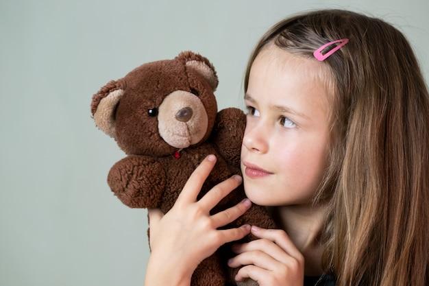 Menina bonita criança brincando com seu ursinho de pelúcia brinquedo.