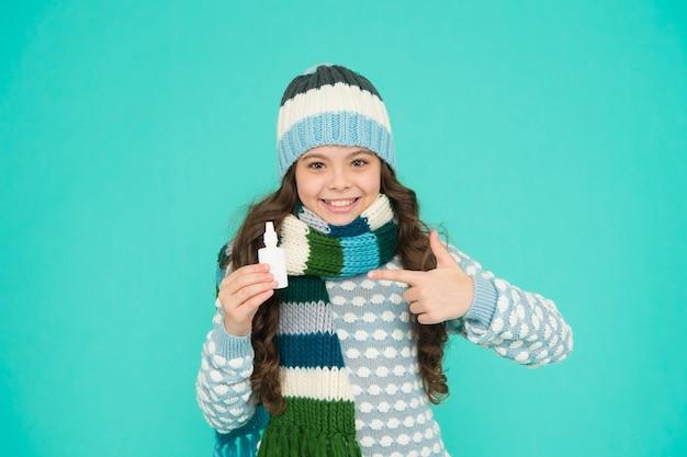 Menina bonita criança com cara feliz e polegar para cima em roupas quentes de malha usa spray nasal, tratamento cobiçoso.