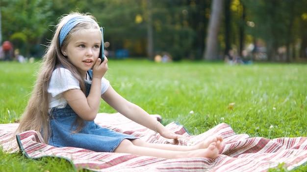 Menina bonita criança conversando em seu telefone móvel no parque de verão.