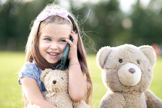 Menina bonita criança falando no celular, sorrindo alegremente ao ar livre no verão.